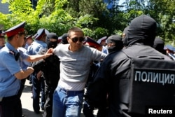 Riot police officers detain a demonstrator during a protest against President Nursultan Nazarbayev's government and an unpopular land reform it has proposed, in Almaty, Kazakhstan, May 21, 2016.