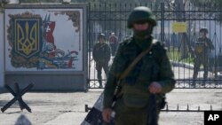 "Russian soldiers guard the entrance to the Ukrainian military base in Perevalne, Crimea. ""We will never accept Russia's occupation and attempted annexation of Crimea,"" said Secretary Tillerson."