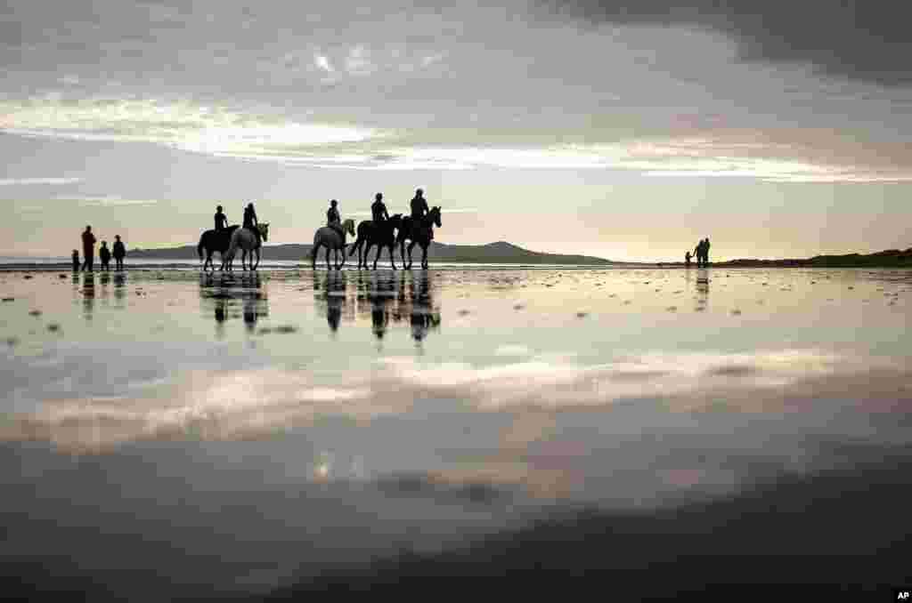 People ride horses along the beach in Portmarnock, County Dublin, Ireland.