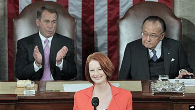 Australian Prime Minister Julia Gillard, center, flanked by Speaker of the House John Boehner, R-Ohio, (l), and Senate President Pro Tempore Daniel Inouye, D-Hawaii, (r), is applauded as she prepares to address a joint meeting of Congress on Capitol Hill