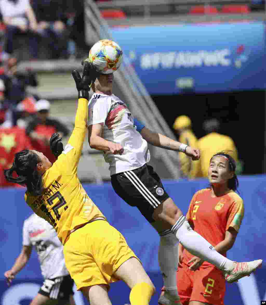 دیدار تیم های چین و آلمان در مسابقات جام جهانی فوتبال زنان در فرانسه؛ پنگ شیمنگ دروازه بان چین برای زدن توپ از روی سر آلکساندرا پوپ، بازیکن آلمان تلاش میکند.