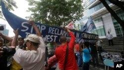 Người biểu tình, khiêng một chiếc thuyền với những khẩu hiệu phản đối các hành động của Bắc Kinh ở Biển Đông đến trước Lãnh sự quán Trung Quốc tại khu tài chính thành phố Makati, phía đông Manila, ngày 3/7/2015.