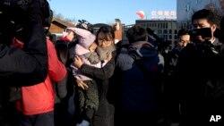 一位家长怀抱刚刚从红黄蓝幼儿园接出的孩子离开。(2017年11月24日)