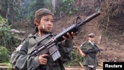 Bé trai 12 tuổi trong phe nổi dậy sắc tộc Karen cầm súng chiến đấu chống quân đội chính phủ Miến Ðiện.