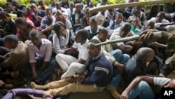 A Kenyan student is prodded in the head by a riot policeman's club inside Nairobi University's main campus, Nairobi, May 20,2014