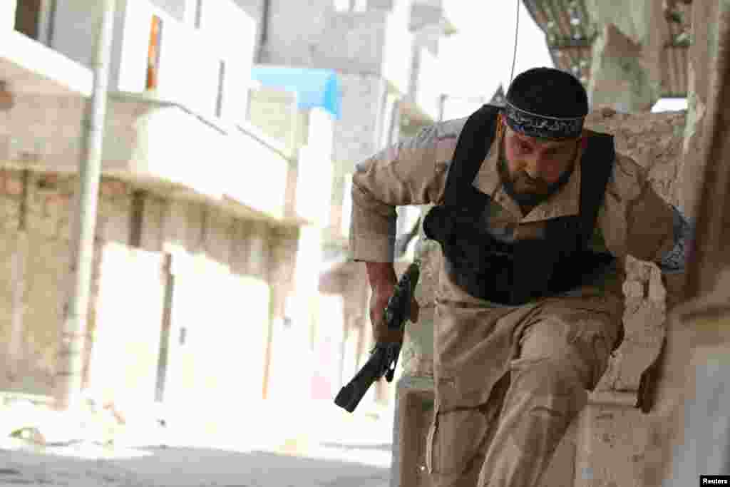 A Free Syrian Army fighter runs for cover near Nairab military airport in Aleppo, Syria, June 12, 2013.