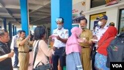 Petugas membagi-bagikan masker bagi pemudik untuk mencegah penyebaran virus corona (VOA/Yudha).