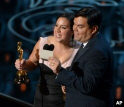 "Kristen Anderson-Lopez, left, and Robert Lopez accept the award for Best Original Song in a Feature Film for ""Let It Go"" from ""Frozen"" during the Oscars at the Dolby Theatre on March 2, 2014, in Los Angeles. (Photo by John Shearer/Invision)"