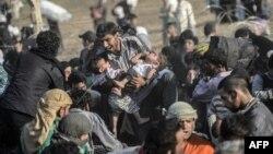 14일 터키와 시리아 국경 지역에서 폭력사태를 피해 달아난 시리아 난민들이 찢어진 철책을 뚫고 들어고 있다.