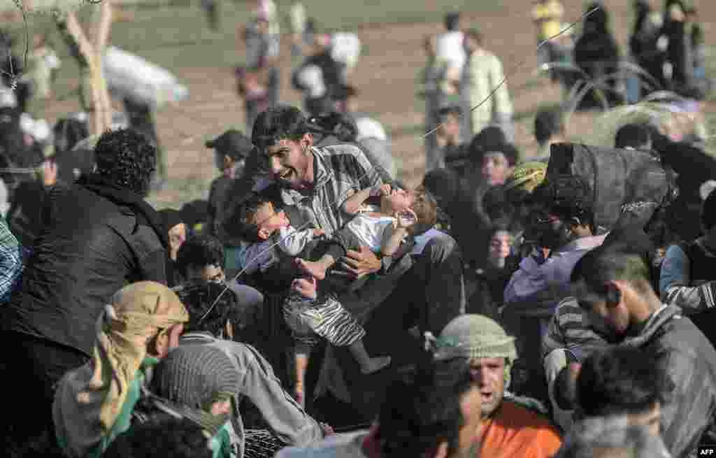 Syrians fleeing the war rush through broken down border fences to enter Turkish territory illegally, near the Turkish border crossing at Akcakale in Sanliurfa province.