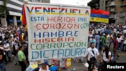 "FILE - Opposition supporters rally against President Nicolas Maduro carrying a sign that reads ""Venezuela is wounded in the heart with hunger, misery, corruption and dictatorship,"" in Caracas, Venezuela, May 10, 2017."