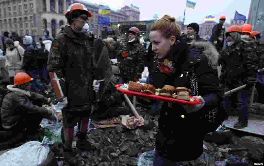 A woman carries sandwiches as anti-government protesters gather in Independence Square, central Kyiv, Feb. 19, 2014.
