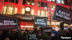 ພວກປະທ້ວງ ຍົກປ້າຍຂຶ້ນ ນອກຮ້ານ Macy's ກ່ອນໜ້າ ການເລີ້ມຕົ້ນ ເປີດການຄ້າຂາຍ ໃນວັນສຸກດຳ ຫຼື Black Friday ຢູ່ລັດ New York, ວັນທີ 27 ພະຈິກ 2014.