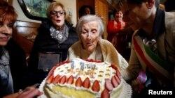Emma Morano, yang ditetapkan sebagai orang tertua di dunia dan yang terakhir yang lahir tahun 1800an, meniup lilin ulang tahun ke-117 di Verbania, Italia utara (29/11). (Reuters/Alessandro Garofalo)