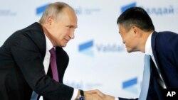 Presiden Vladimir Putin (kiri) berjabat tangan dengan CEO Alibaba, Jack Ma (foto: dok).