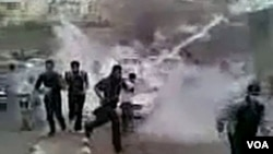 Para demonstran di Daraa menghindar dari tembakan gas air mata pasukan keamanan (23/3).