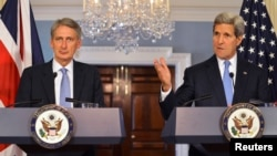U.S. Secretary of State John Kerry (R) makes remarks as Britain's Foreign Secretary Philip Hammond looks on, during a press availability at the State Department in Washington, Oct. 8, 2014.