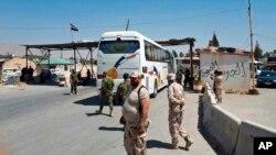 Pasukan Suriah mengawasi upaya evakuasi anggota kelompok pemberontak Laskar Islam dari kota Douma (2/4).