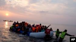 Des volontaires aident des migrants et des refugies qui ont réussi à traverser le mer Aggée en provenance de la Turquie, à Lesbos, Grèce, 20 mars 2016.