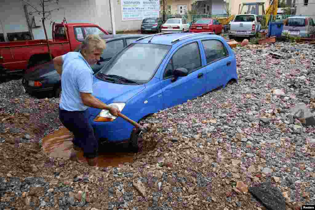 A local person shovels mud blocking a car, following heavy rainfall in Malia on the island of Crete, Greece.