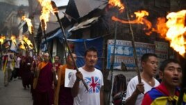 Exile Tibetans carry torches as they participate in a candlelit vigil in Dharmsala, India, June 21, 2012.