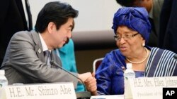 Japanese Prime Minister Shinzo Abe, left, shakes hands with Liberian President Ellen Johnson Sirleaf at a symposium on human security held on the sidelines of the Tokyo International Conference on African Development in Yokohama, Japan, June 2, 2013.