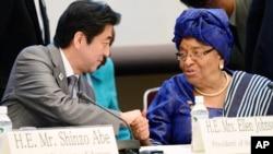 ທ່ານ Shinzo Abe (ຊ້າຍ) ນາຍົກລັດຖະມົນຕີຍີ່ປຸ່ນ ຈັບມືກັບ ປະທານາທິບໍດີ Liberia ທ່ານນາງ Ellen Johnson Sirleaf ທີ່ກອງປະຊຸມເລື້ອງຄວາມໝັ້ນຄົງຂອງມະນຸດຊົນ ທີ່ຈັດຂຶ້ນ ນອກກອງປະຊຸມ ສາກົນໂຕກຽວ ກ່ຽວກັບ ການພັດທະນາທະວີບອາຟຣິກາ ຢູ່ໃນເມືອງ Yokohama ທາງທິດໃຕ້ຂອງນະຄອນຫລວງໂຕກຽວTokyo ໃນວັນທີ 2 ມິຖຸນາ, 2013.