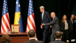 Kosovo Prime Minister Isa Mustafa welcomes U.S. Secretary of State John Kerry to a joint press conference after Kerry's arrival in Kosovo's capital Pristina airport, Dec. 2, 2015.