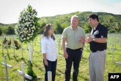 This photo taken on March 12, 2016 shows former US vice-president Al Gore (C) talking to Philippine Senator Loren Legarda (L) and Mayor Alfred Romualdez during a visit to the mass grave for victims of super typhoon Haiyan, in Tacloban City, central Philippines.