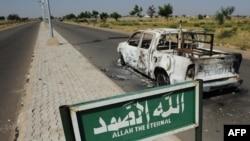 Une camionnette de patrouille de police brûlée reste abandonnée sur le bord d'une route déserte à Damaturu, dans l'État de Yobe, au Nigeria le 7 novembre 2011.