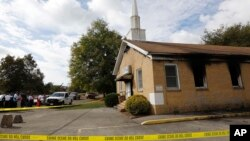 """FILE - Area residents and church members look on as authorities investigate a fire at Hopewell Baptist Church in Greenville, Mississippi, Nov. 2, 2016. """"Vote Trump"""" was spray-painted on an outside wall of the African-American church."""