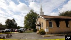 Penduduk sekitar dan jemaat gereja terus memperhatikan otoritas keamanan yang menyelidiki kebakaran di Gereja Baptis Hopewell (2/11). Greenville, Mississippi. (foto: AP Photo/Rogelio V. Solis)