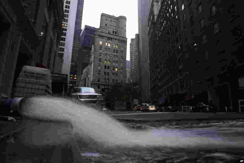 Water gushes from a hose as it is pumped out of a basement in New York's financial district, Oct. 31, 2012.