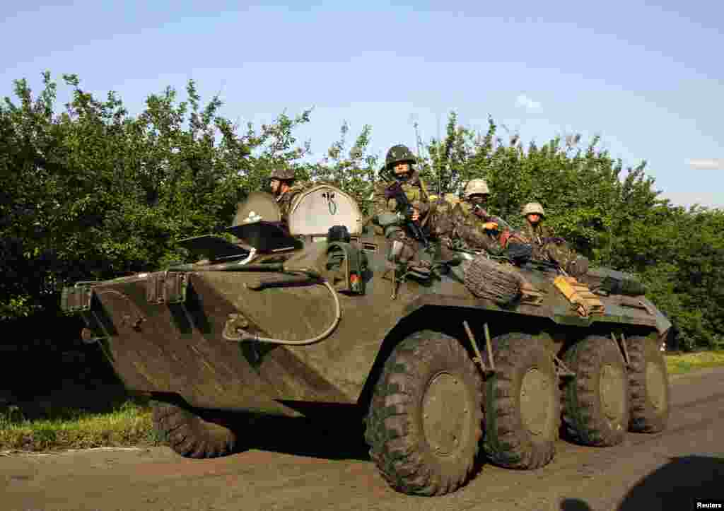 Ukrainian paratroopers ride atop an armored personnel carrier in the village of Starovarvarivka, Ukraine, May 15, 2014.