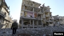 A fighter of Free Syrian Army's Tahrir al Sham brigade walks in front of building destroyed during yesterdays Syrian Air force air strike in Mleha suburb of Damascus January 21, 2013.