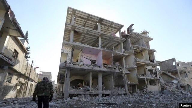 Wani mayakin 'yan tawaye akan hanyarshi a gaban wani gini da sojojin gwamnati suka fasa a unguwar Mleha dake birnin Damascus Junairu 21, 2013.