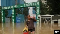Seorang pria membawa air minum kemasan saat melintasi jalan yang banjir menyusul hujan lebat yang membanjiri dan menewaskan sedikitnya 33 orang pekan ini di kota Zhengzhou, provinsi Henan, China, 23 Juli 2021. (Foto: Noel Celis / AFP).