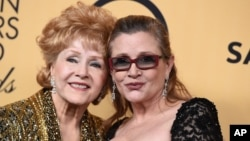 Debbie Reynolds, winner of the Screen Actors Guild lifetime award (left) and Carrie Fisher pose in the press room at the 21st annual Screen Actors Guild Awards at the Shrine Auditorium, Jan. 25, 2015, in Los Angeles.