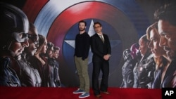 "Chris Evans, left, and Robert Downey Jr. pose for photographers at the photo call of the film ""Captain America Civil War"" in London, April 25, 2016."