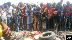 Mutane sunyi dafifi kewaye da inda boma-boman ya tashi a Maiduguri a ranar 14 ga watan Maris 2014.