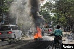 Nyala api dan asap akibat ban yang dibakar, terlihat di tengah jalan saat berlangsungnya protes menentang kudeta militer, di Mandalay, Myanmar 1 April 2021. REUTERS / Stringer