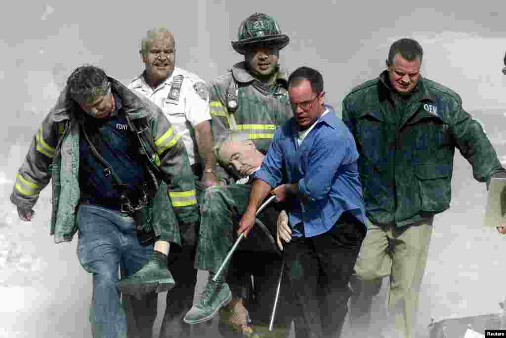 Rescue workers carry fatally injured New York City Fire Depatment Chaplain, Fether Mychal Judge, from one of the World Trade Center towers.