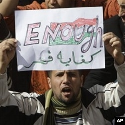 A Libyan protester holds up a sign against Libyan Leader Moammar Gadhafi during a demonstration, in Tobruk, Libya, February 23, 2011