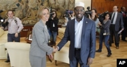 Spain's Defence Minister Carme Chacon, left shakes hands with Somaila's President Sheik Sharif Sheik Ahmed at the Spanish Defence Ministry in Madrid, Monday, Sept. 27, 2010. Sheik Sharif Sheik Ahmed is in Madrid to attend the XVIII international contact