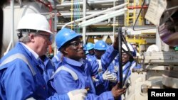 FILE - Ghana's President John Atta Mills turns on the valve to allow the first barrel of crude to flow from the Jubilee offshore oil field.