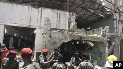 People gather at the bombed office of ThisDay, an influential daily newspaper, Abuja, Nigeria, April 26, 2012.