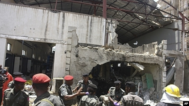 Police and rescuers stand in front of the bombed office of ThisDay, an influential daily newspaper in Abuja, Nigeria, April. 26, 2012.