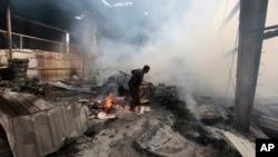 Seorang pekerja mencari orang-orang dibawah puing pabrik makanan yang terkena serangan udara Saudi di Sana'a, Yaman Selasa (9/8).