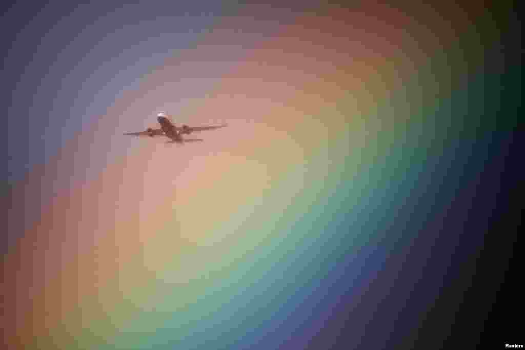 A British Airways aeroplane flies near a rainbow on its way to Heathrow Airport in London, Britain.