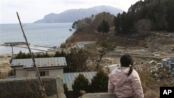 Manami Kon, 4, waits for her parents and younger sister who are still missing after the March 11 massive earthquake and tsunami, in Miyako, northern Japan, March 22, 2011